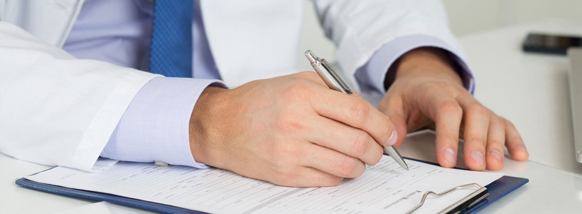 A doctor filling out paperwork representing the expertise of Tarun Jolly in New Orleans, LA